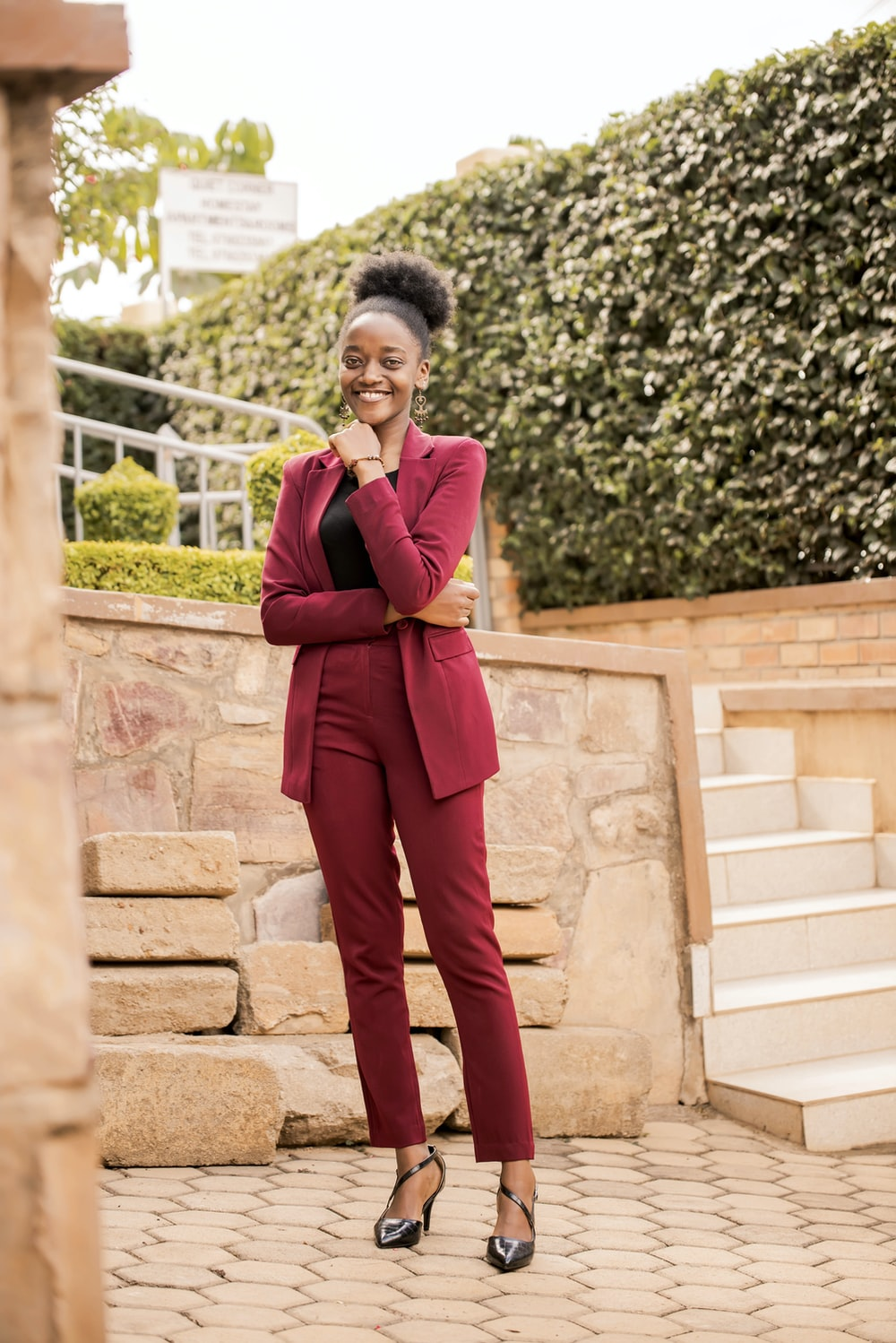 woman in red blazer and brown pants standing on brown concrete stairs