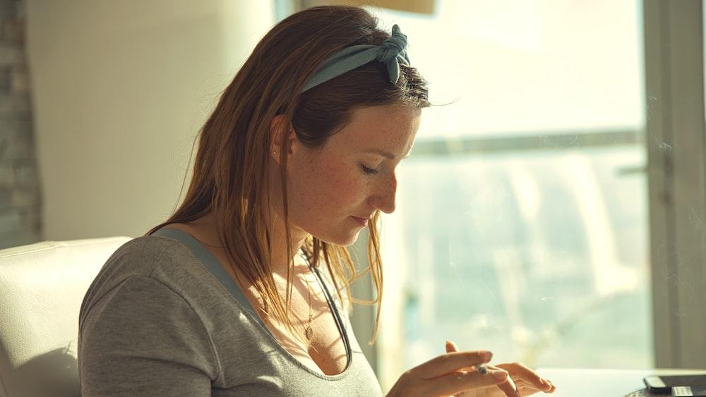 woman in gray long sleeve shirt wearing white headphones