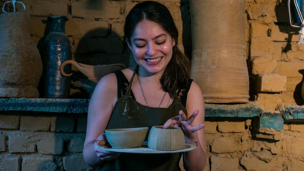 woman in black tank top holding white ceramic bowl