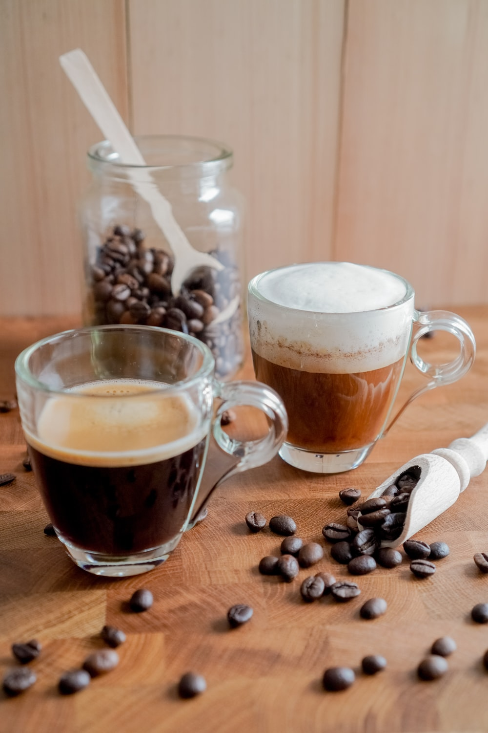 clear glass mug with coffee beans on brown wooden table