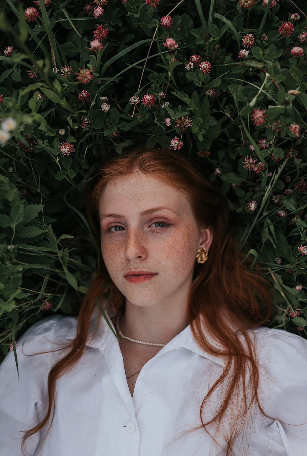 woman in white button up shirt lying on green grass