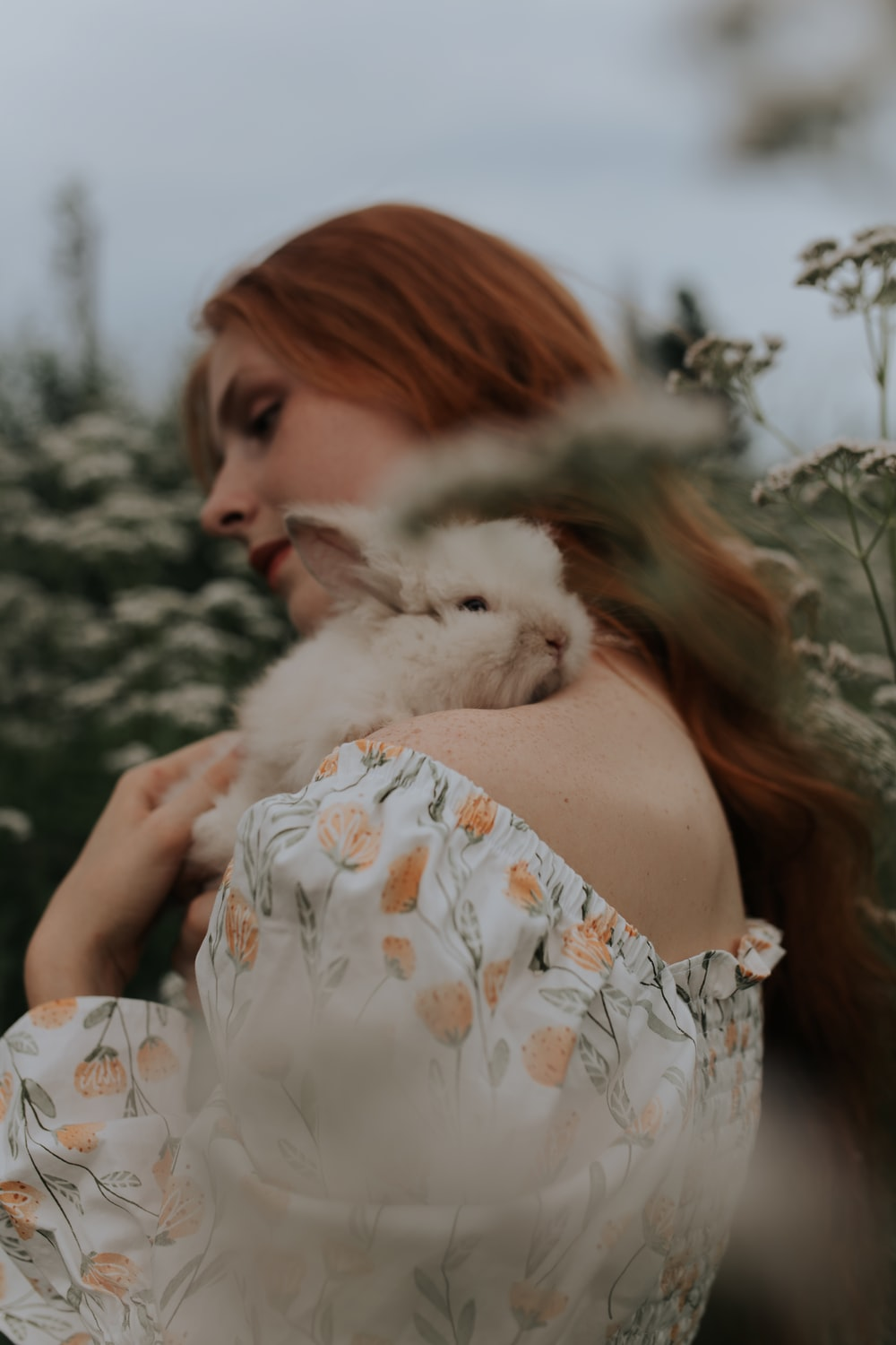 woman in white and orange floral dress holding white fur animal