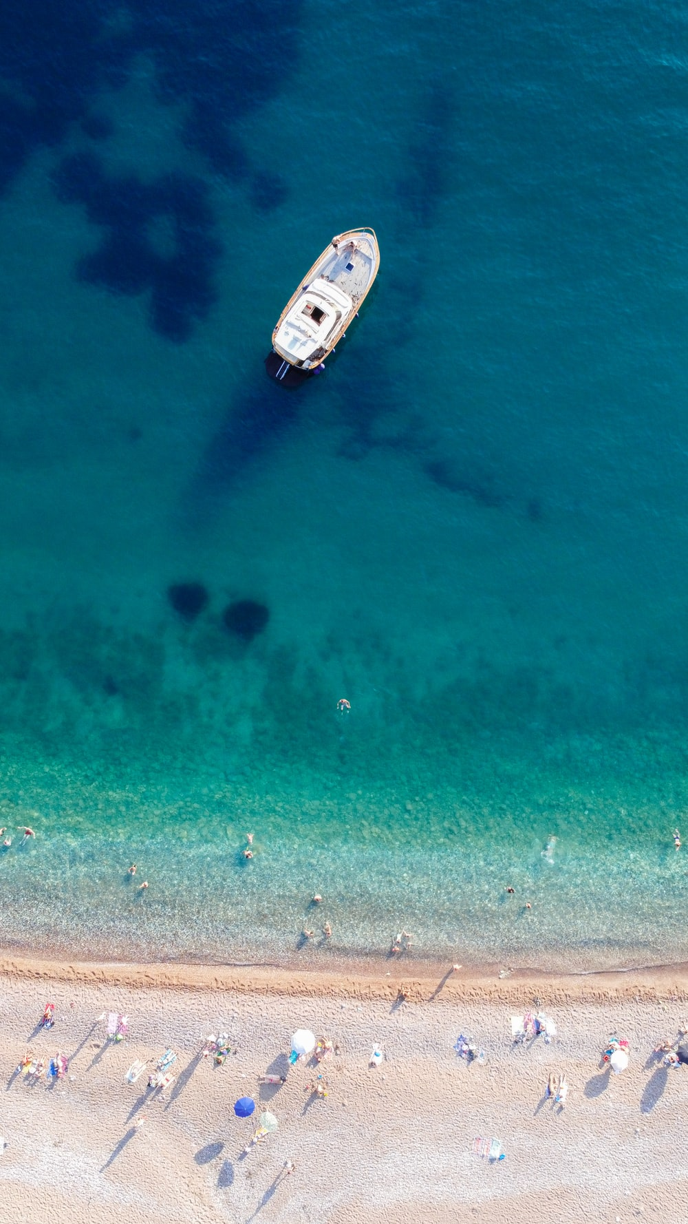 white and black boat on blue sea water during daytime
