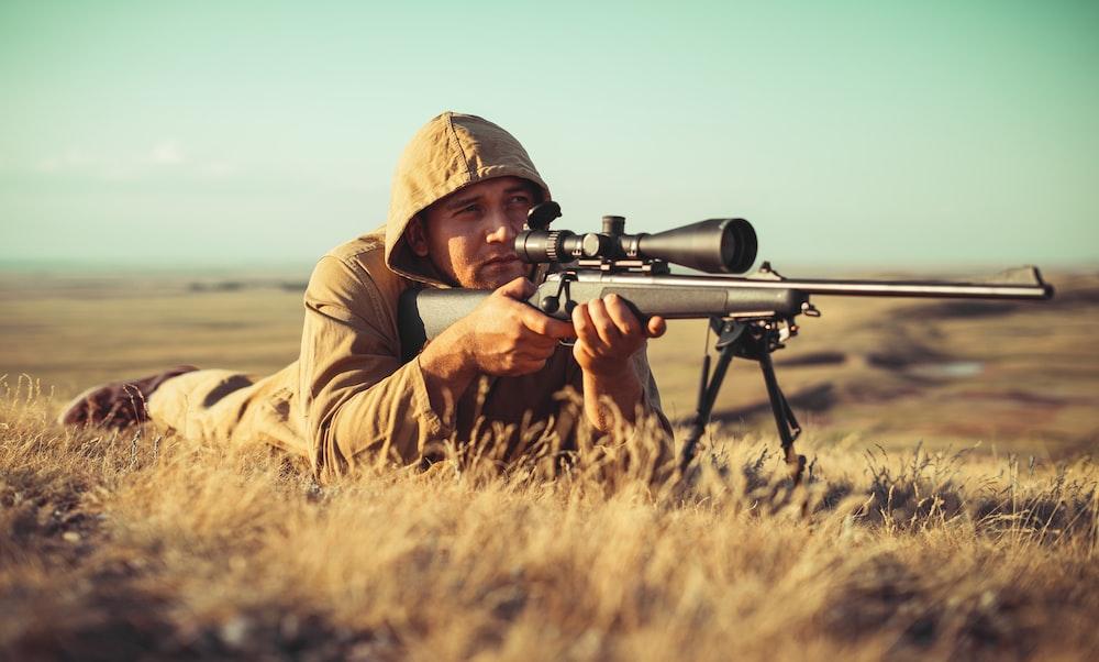 man in brown jacket holding black rifle