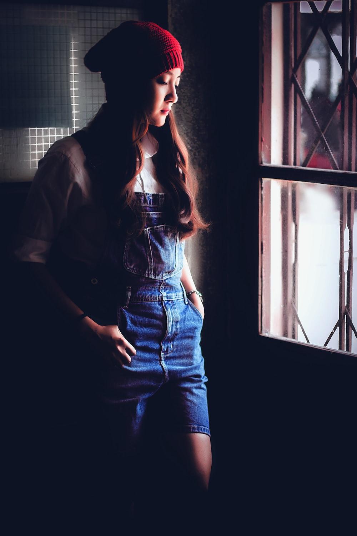 woman in blue denim jeans standing beside window