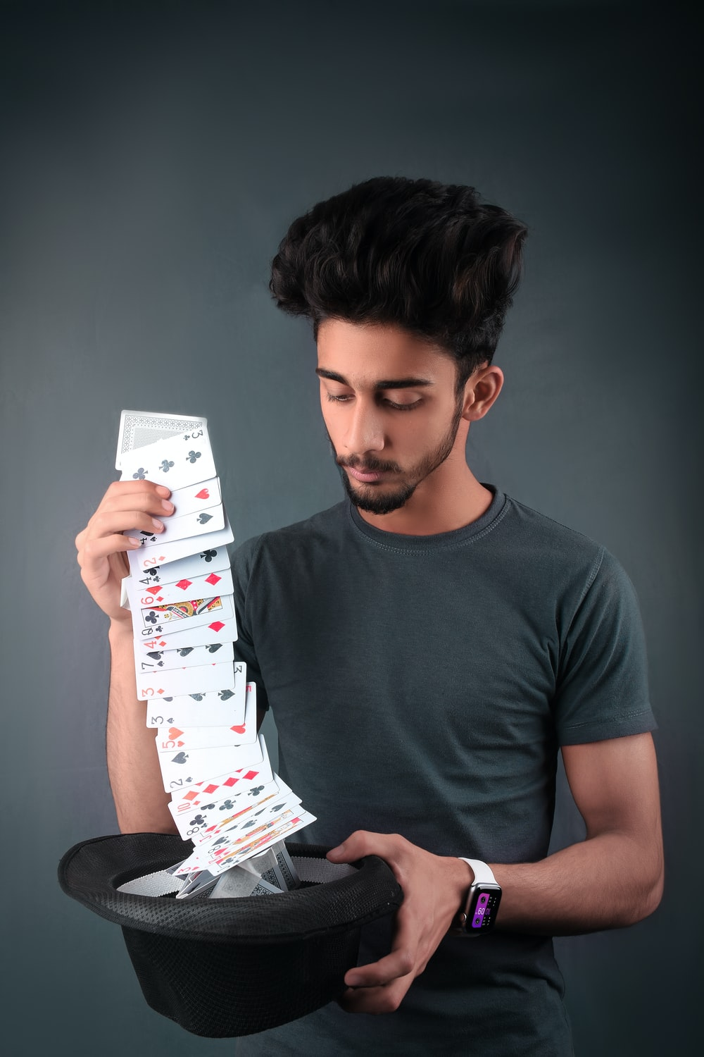 man in gray crew neck t-shirt holding white and red playing cards
