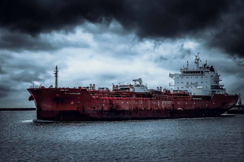 red and white ship on sea under white clouds