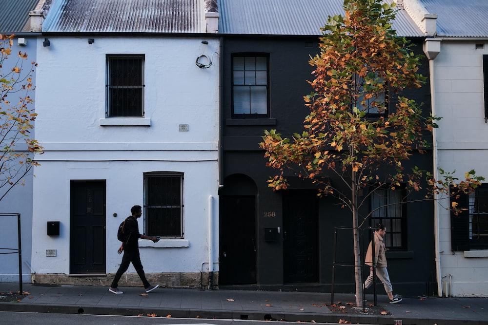 man in black jacket walking on sidewalk near white concrete building during daytime