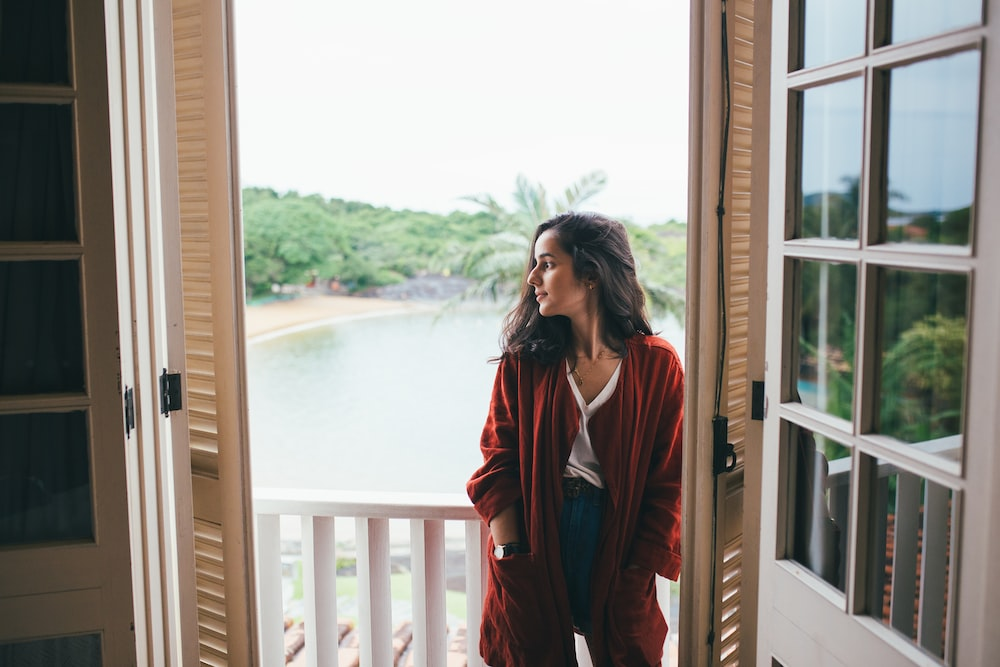 woman in red long sleeve shirt standing beside window during daytime