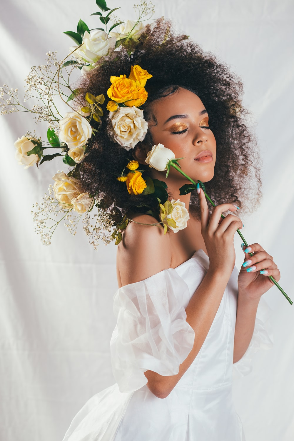 woman in white off shoulder dress holding yellow and white flower bouquet