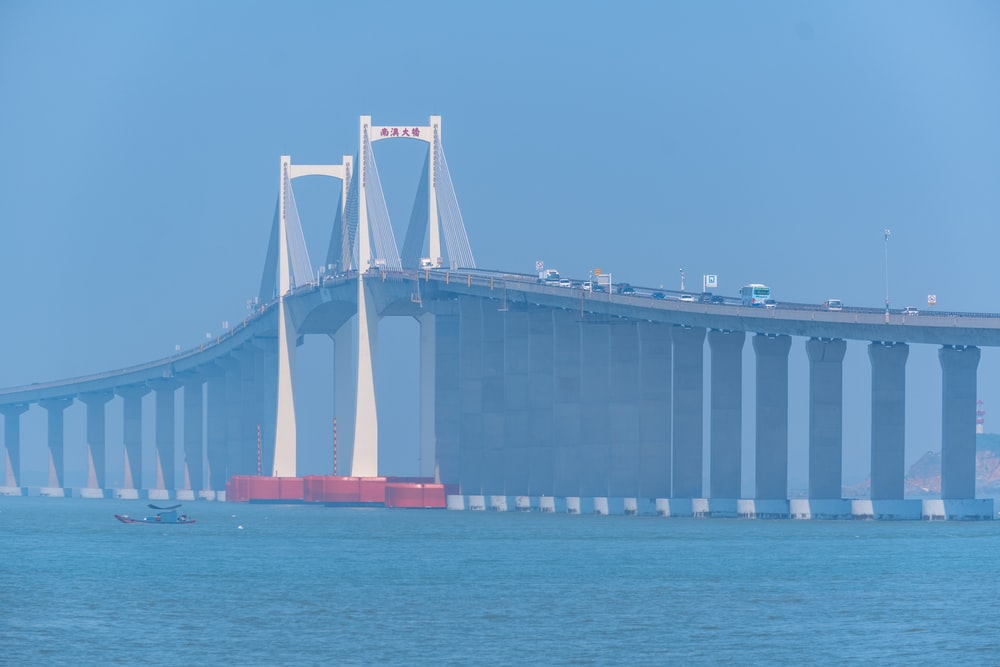 white and red bridge over blue sea during daytime