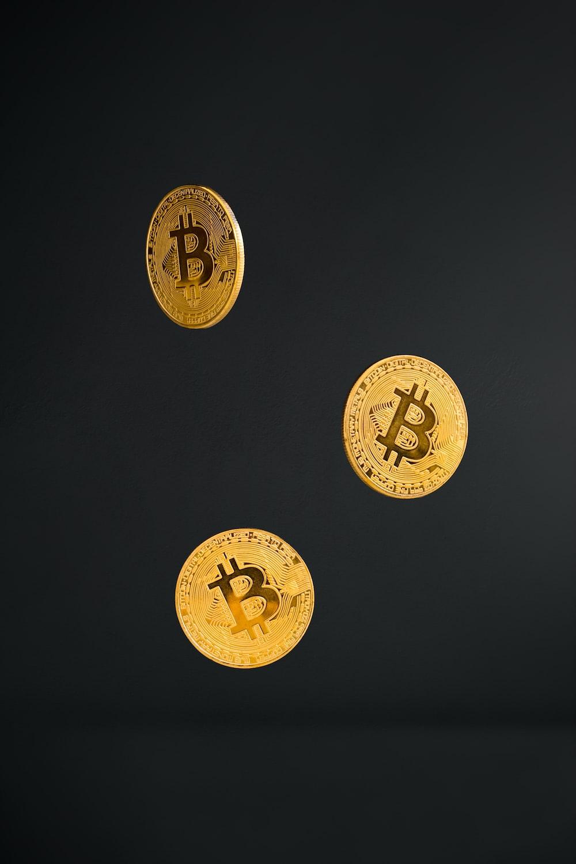 3 gold round coins on black background