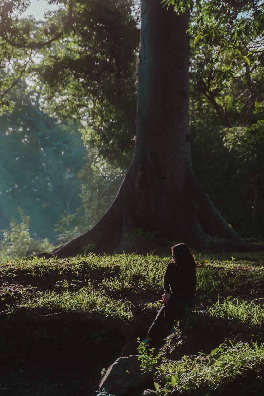 woman in black jacket standing beside tree during daytime