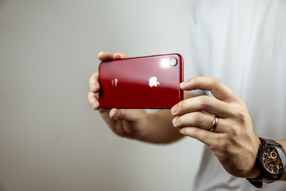 person holding red iphone 7 plus