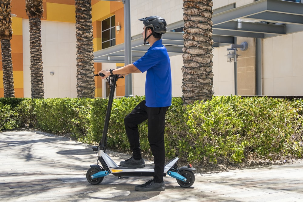 man in blue dress shirt and black pants riding blue and black kick scooter during daytime