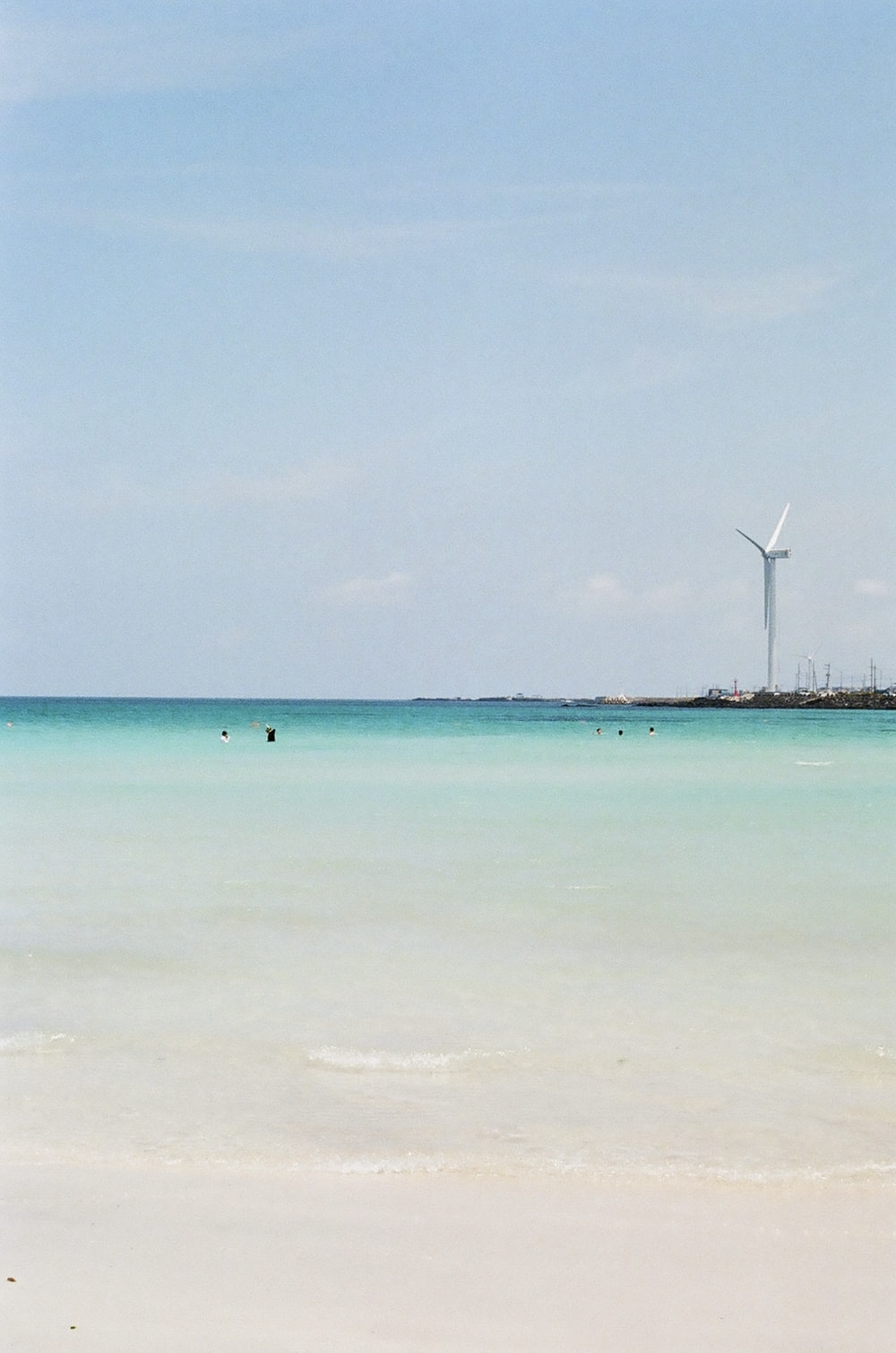 white wind turbines on green sea under blue sky during daytime