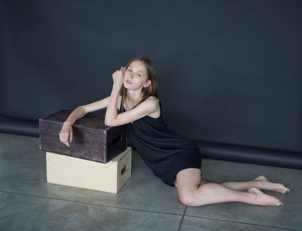 woman in black tank top and blue denim shorts sitting on black wooden box