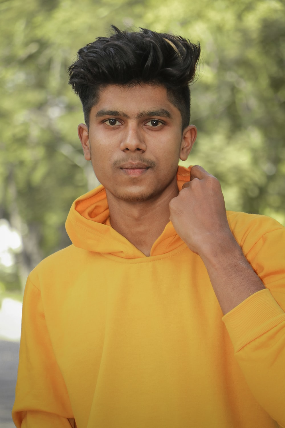 man in yellow hoodie holding his chin