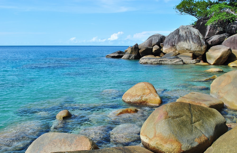 brown rocks on blue sea under blue sky during daytime