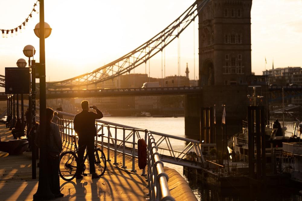 man in black jacket and pants standing on bridge during daytime