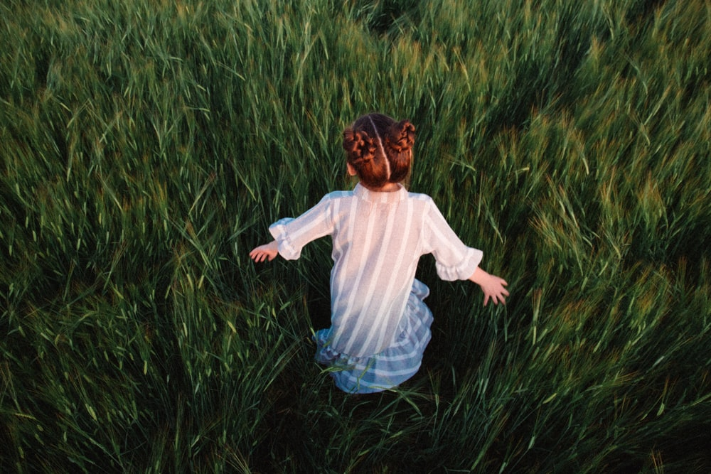 girl in white shirt and blue denim jeans running on green grass field during daytime