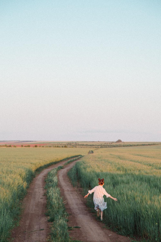 man in white dress shirt walking on brown dirt road between green grass field during daytime