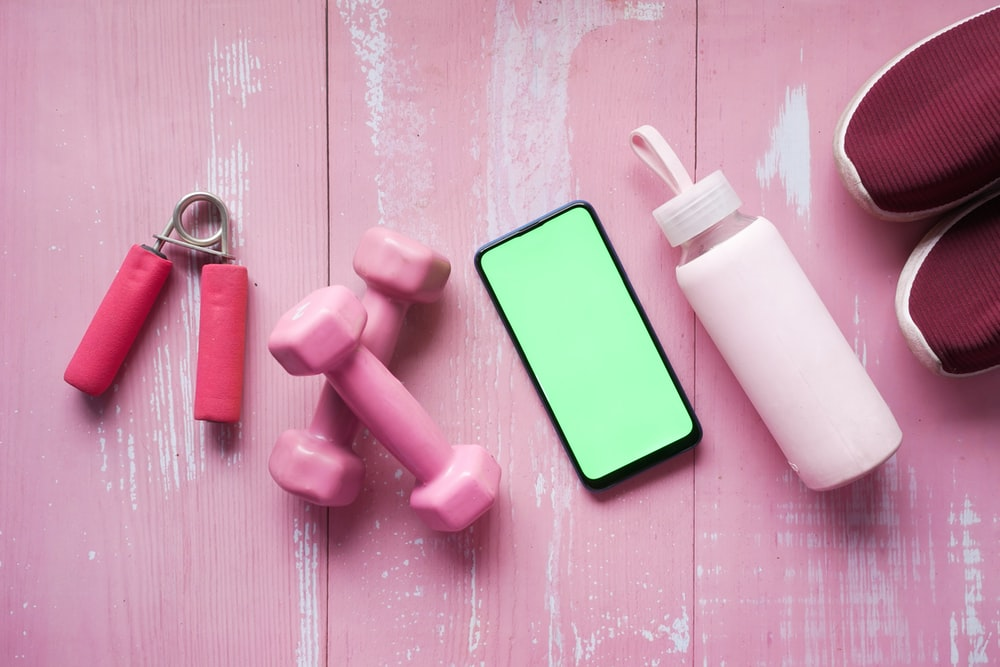 person holding pink and white plastic bottle