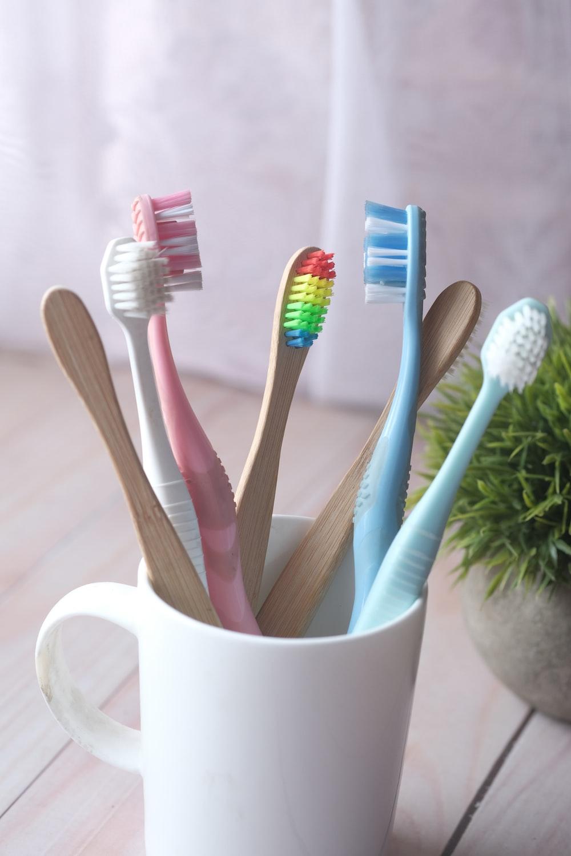 white and blue toothbrush in white ceramic mug