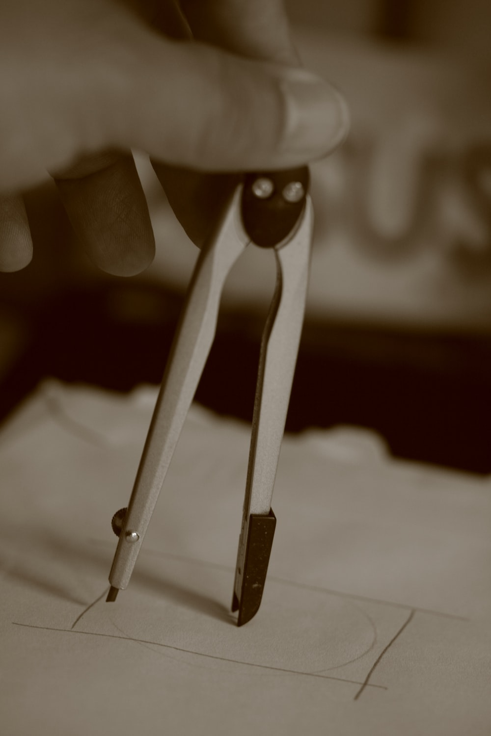 gray scale photo of person holding paper clip