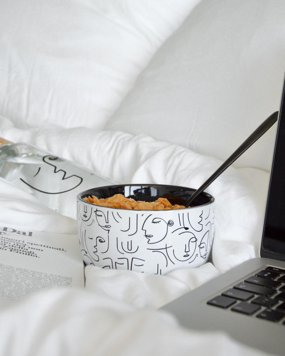 white and black ceramic mug with spoon