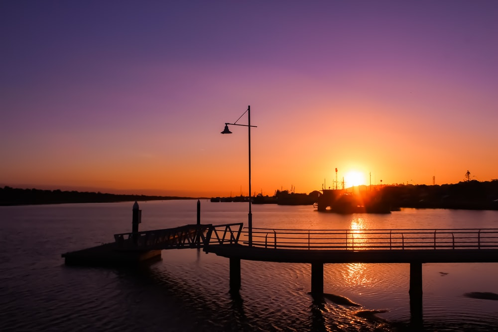 silhouette of a person standing on a dock during sunset