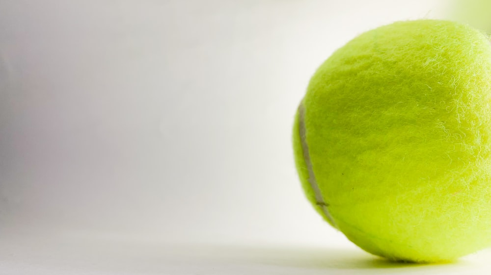 green tennis ball on white surface