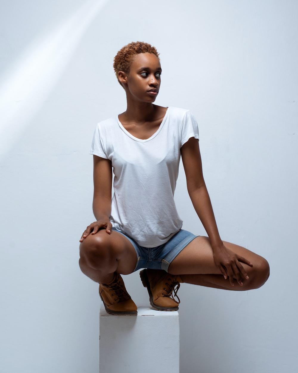 girl in white crew neck t-shirt and blue denim shorts sitting on floor