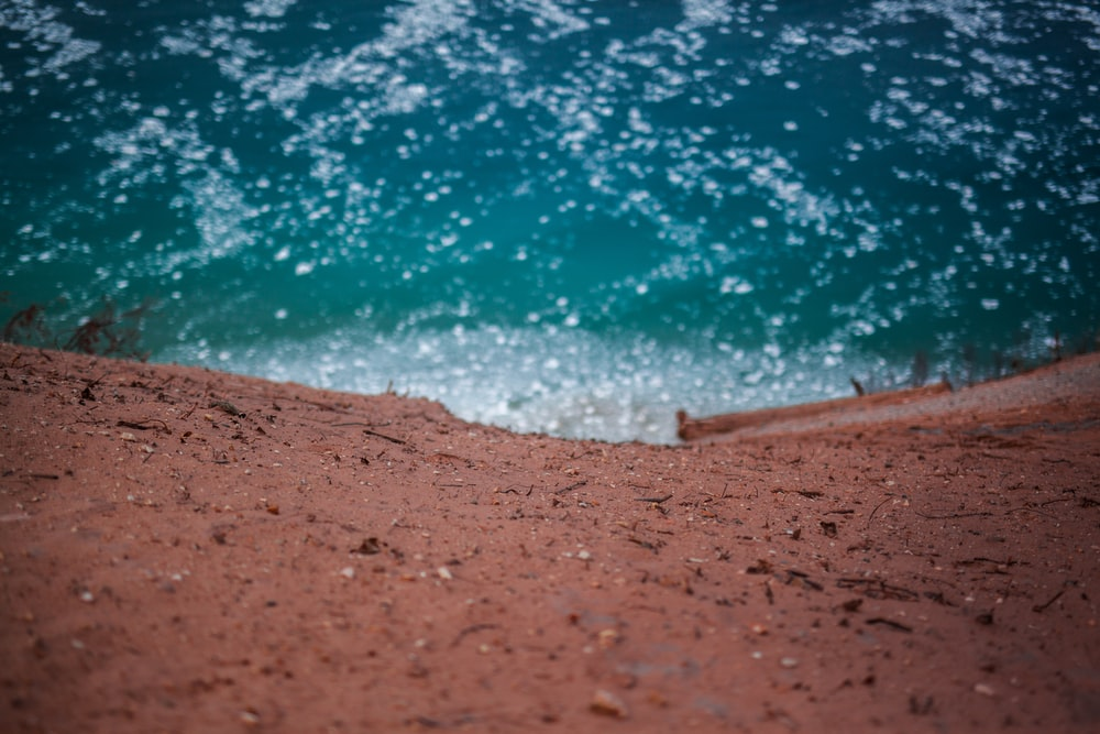 brown sand near blue body of water during daytime