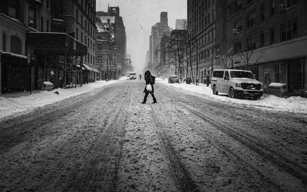 grayscale photo of person walking on road