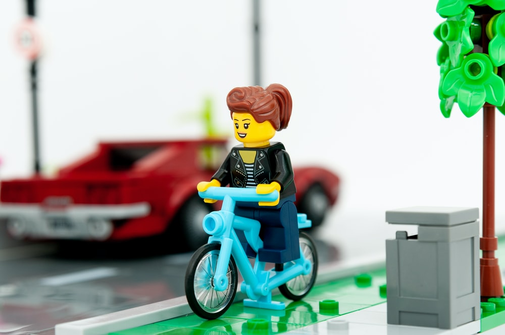 lego minifig riding on bicycle