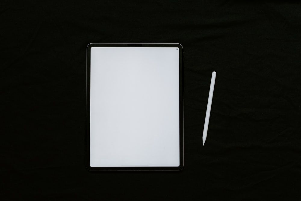 white tablet computer on black textile