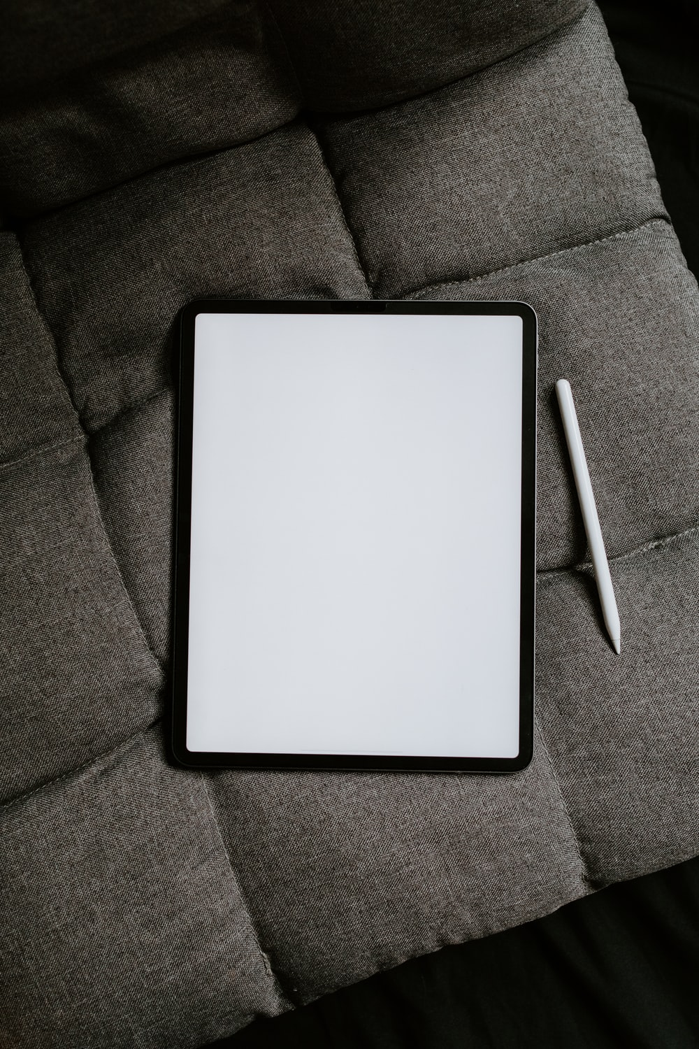 white tablet computer on gray textile
