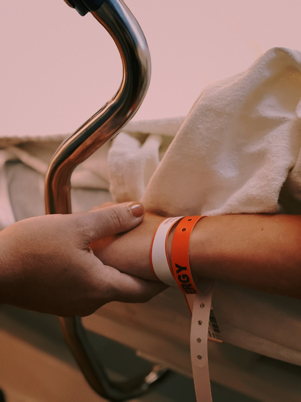 person wearing orange and white silicone band