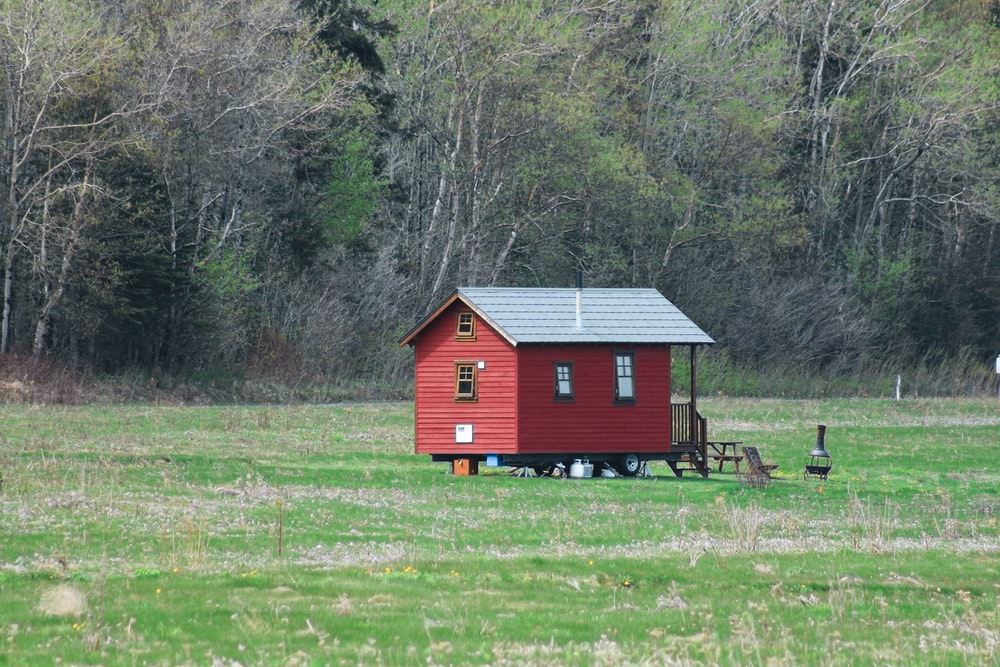 red and white wooden house on green grass field