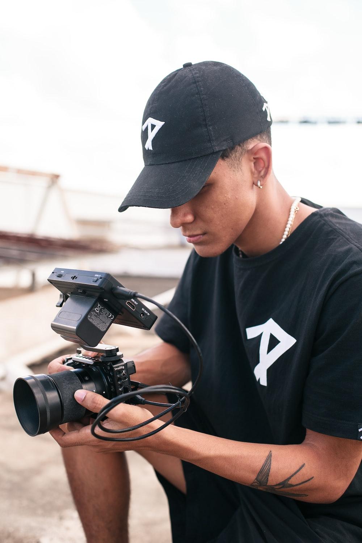 man in black nike crew neck shirt using black dslr camera
