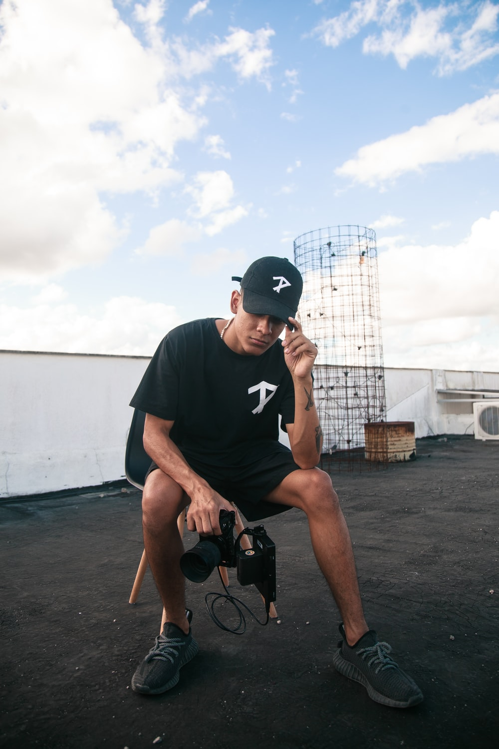 man in black crew neck t-shirt and black nike cap sitting on brown wooden chair