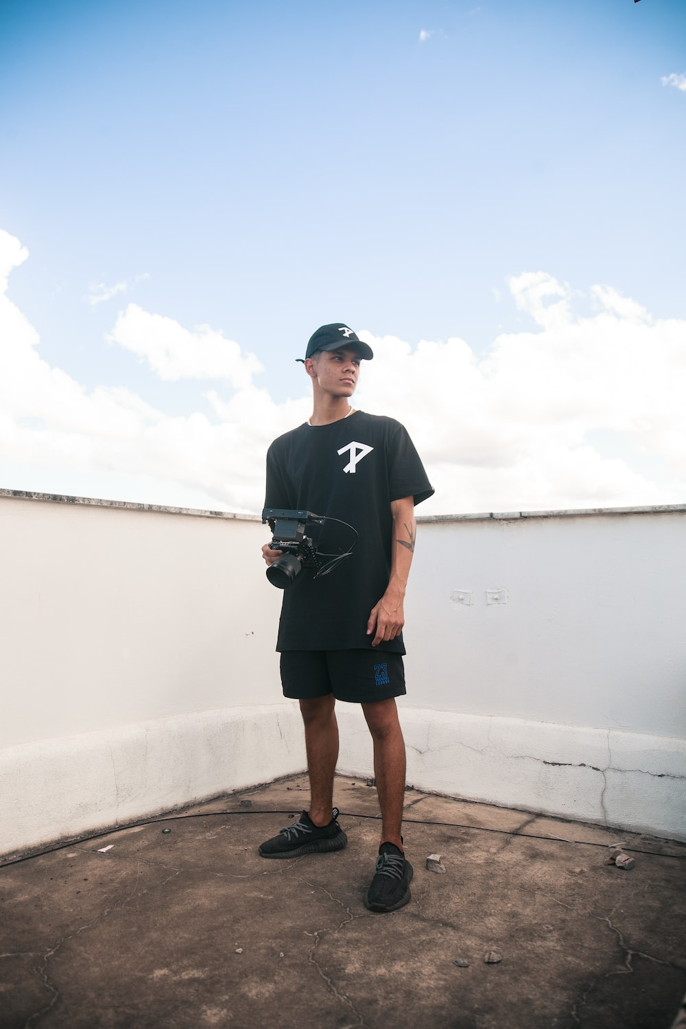 man in black crew neck t-shirt and black shorts standing on brown wooden dock during