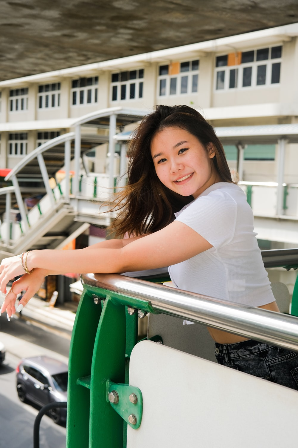woman in white t-shirt leaning on green metal railings