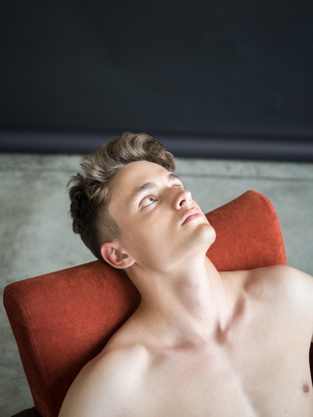 topless man lying on red sofa