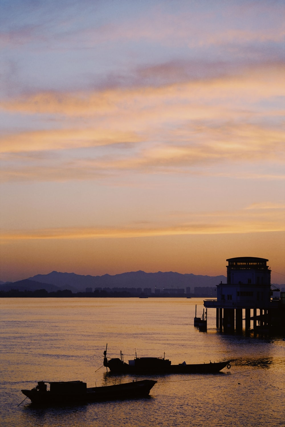 silhouette of a dock on a body of water during sunset