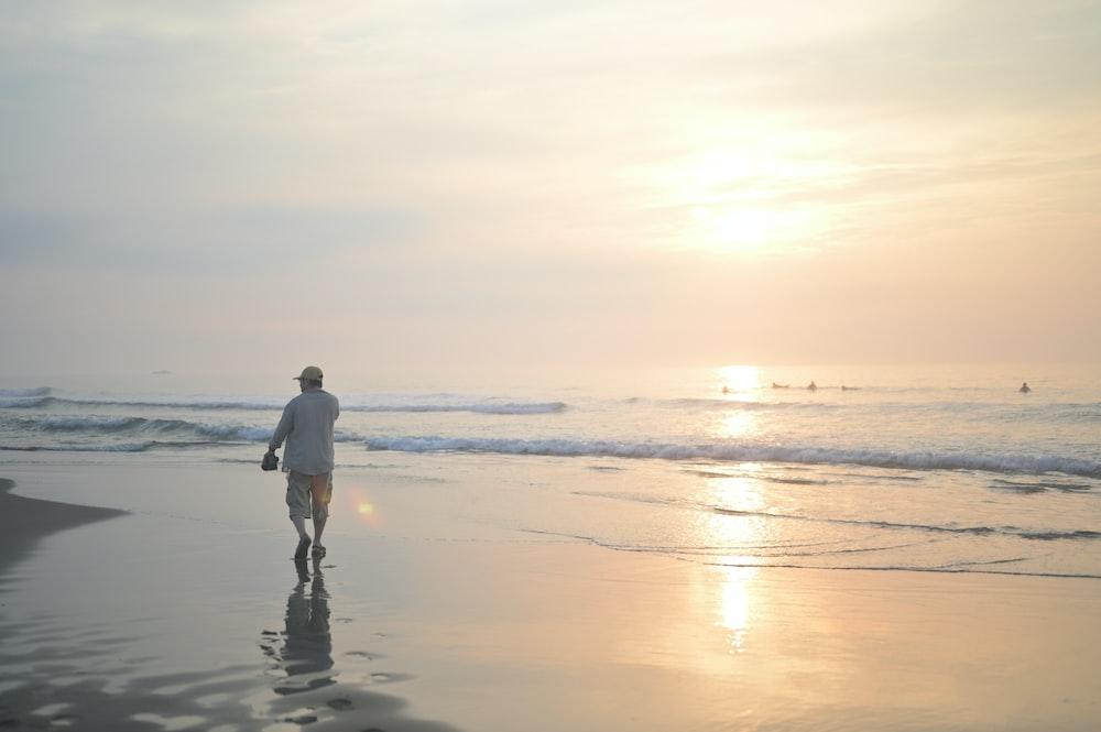 man in white shirt and black pants walking on beach during sunset