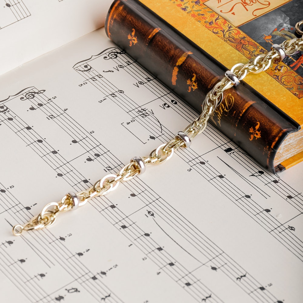 gold chain necklace on musical note sheet