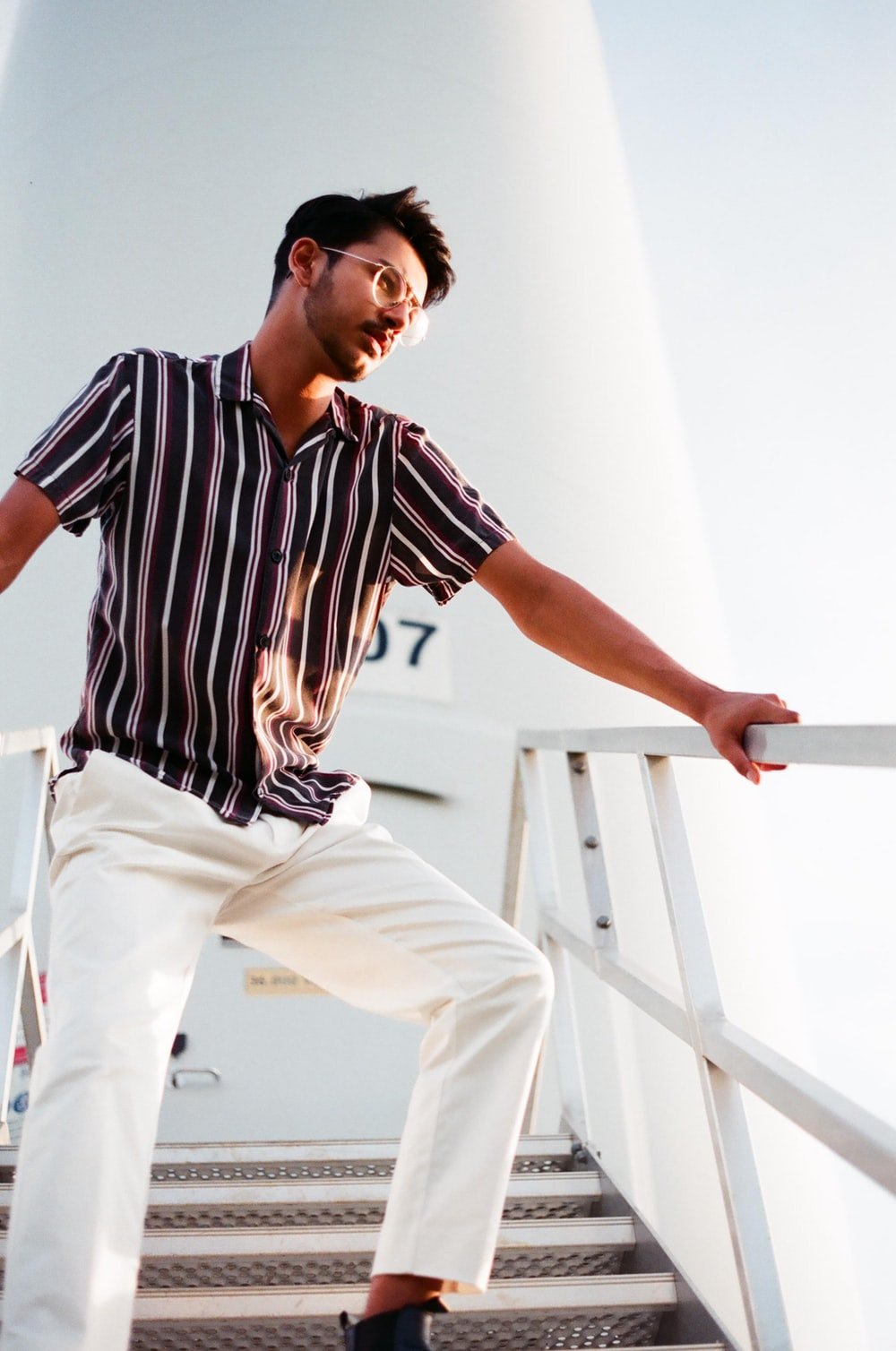 man in black and white stripe shirt and white pants sitting on white wooden staircase