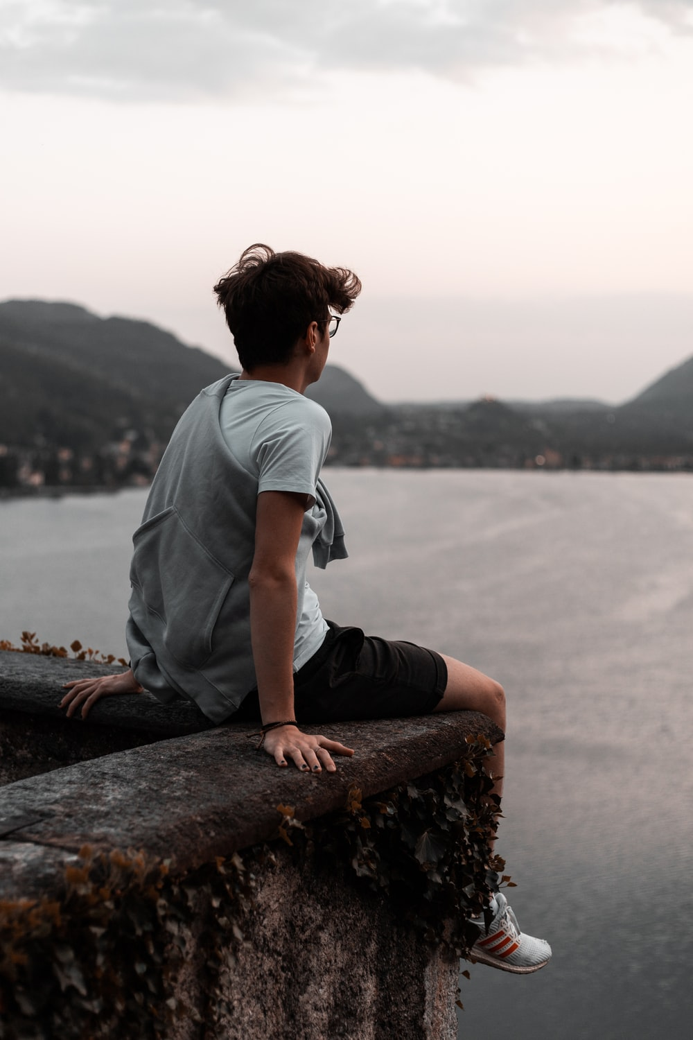 man in grey t-shirt and black pants sitting on brown rock near body of water